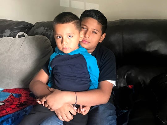 Randy Lopez-Mulato, 10, holds his brother Andy, 3, in their Home in southwest Detroit on Oct. 26, 2017. Their father, Noe Lopez-Mulato, was deported to Mexico Oct. 23, 2017.