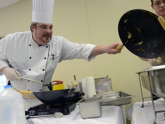 Chef Sean O'Rourke serves up a dish from his table with Wok Inn Carry Out, Sunday, Jan 25, 2015, during the annual Taste of the Thumb in Lexington.
