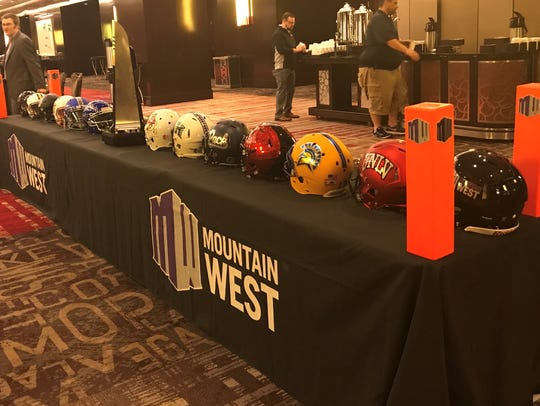 Helmets of the league's teams flank the Mountain West