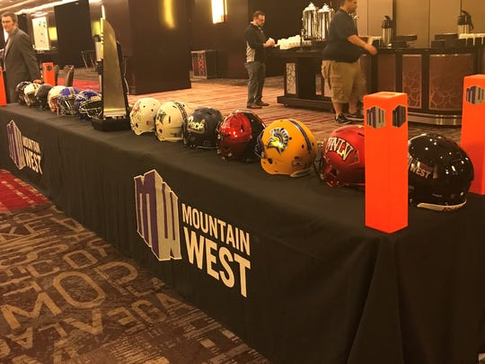 Helmets of the league's teams flank the Mountain West championship trophy at the league's annual football media days at the Cosmopolitan in Las Vegas.