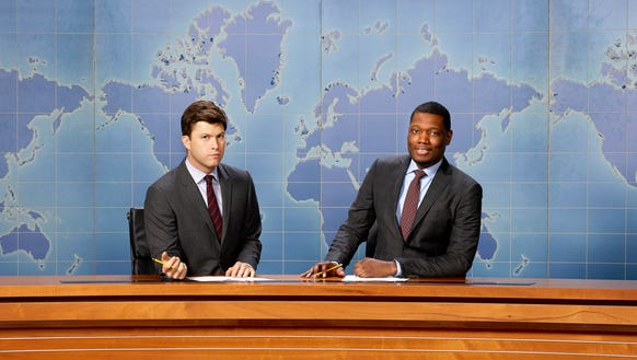 "Colin Jost (left) and Michael Che sit at the anchor desk on ""Saturday Night Live."""