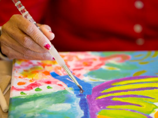 Maria Flores, 76, of El Mirage, takes a painting class