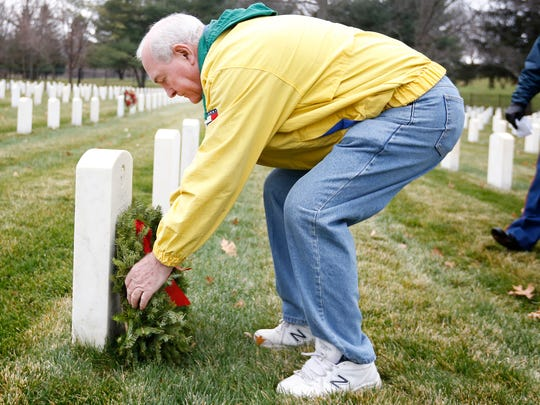 """Arctic League president Bob Haskins lays a wreath at the headstone of James L. Loftus who was the young veteran who inspired the start of the non-profit organization more than 100 years ago when a group of men found Loftus near railroad tracks. The group affectionately called Loftus """"Friday"""" for the day of the week he was found."""
