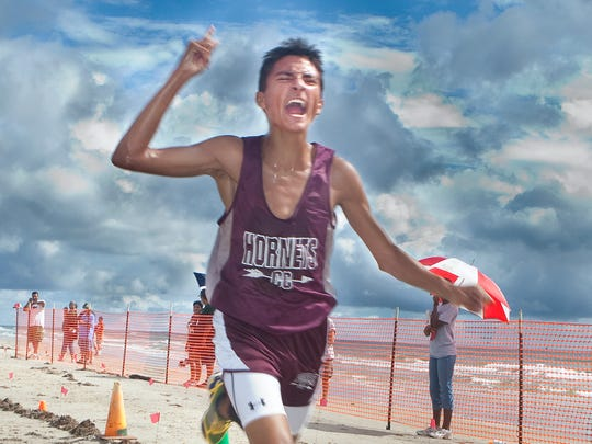 Flour Bluff senior Andre Fuqua, 17, celebrates crossing the finish line first at the Flour Bluff Invitational cross country meet on Malaquite Beach at the Padre Island National Seashore.