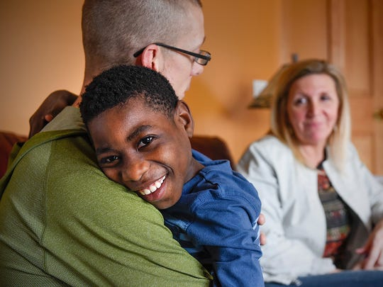 Jason and Jessica Neal play with their adopted son Emmanuel Thursday, March 31, at their home in Andover as they talk about the adoption process from Liberia. The Neals lived in Sartell when they started the adoption process.