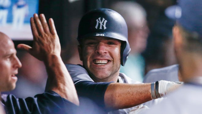 New York Yankees' Austin Romine celebrates in the dugout after scoring on a double and two Cleveland Indians errors on a play during the seventh inning of a baseball game, Saturday, July 14, 2018, in Cleveland.