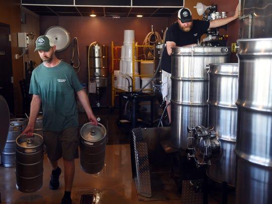 Dennis Joyner (left) moves kegs to the back of the