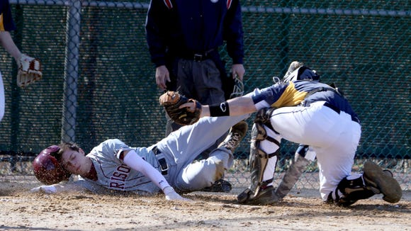 Harrison's Will Marriott is tagged out by Pelham catcher Michael Kakos while trying to score in the first inning of a  varsity baseball game at Pelham April 5, 2017. Harrison defeated Pelham 2-0.