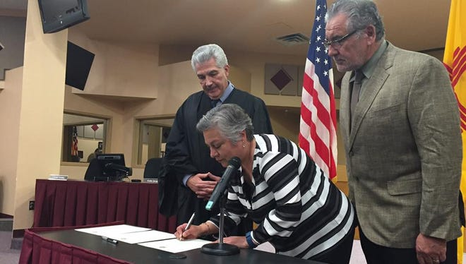 Las Cruces Public Schools Board President Maria Flores signs the oath administered by District Judge Fernando Macias at a swearing-in ceremony on March 1, 2017, as her husband and Macias look on. Flores begins her third term on the board.