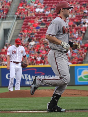 Arizona Diamondbacks Paul Goldschmidt heads for home plate after hitting a home run against the Cincinnati Reds pitcher Anthony DeSclafani, left, in the first inning of their baseball game in Cincinnati, Saturday, Aug. 22, 2015.