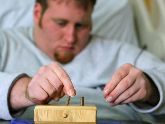 Recovering heroin addict Jason Malone struggles putting pegs into a peg board as part of his home therapy. Jason overdosed
