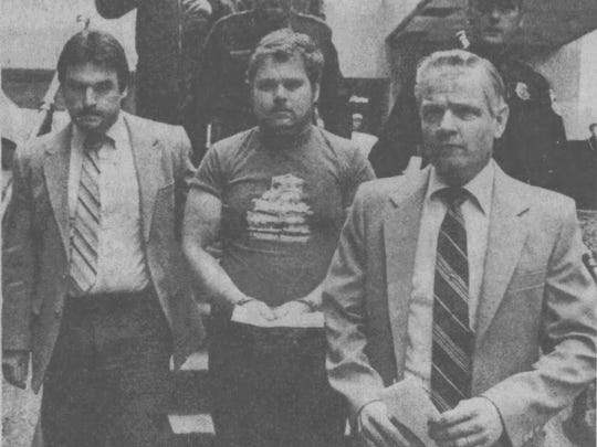 A handcuffed James Wales is taken to jail in March 1984, after being arraigned in Cheri Lindsey's murder. At left, Binghamton police Sgt. John Butler.