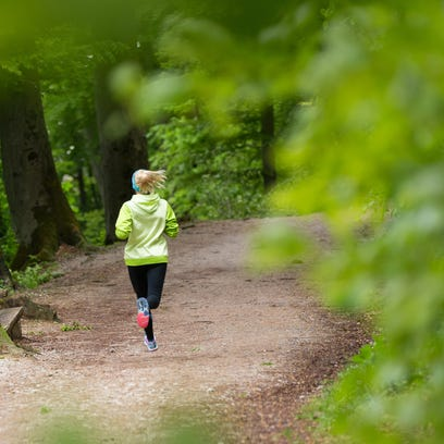 Sporty young female runner in forest.  Running woman.