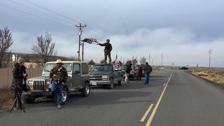People wave American flags near the Malheur National