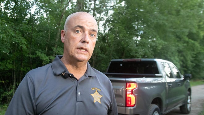 Sheriff Chip Hughes speaks with reporters at the crime scene.
