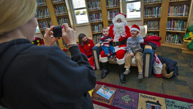 Will 18 mths, and Jack 5 yrs Aulgur sit with Santa as Nanny Shannon Joyce gets a picture in 2011 at Woodlawn Library. County libraries will be accepting donations of prom dresses and tuxes on Jan. 3.