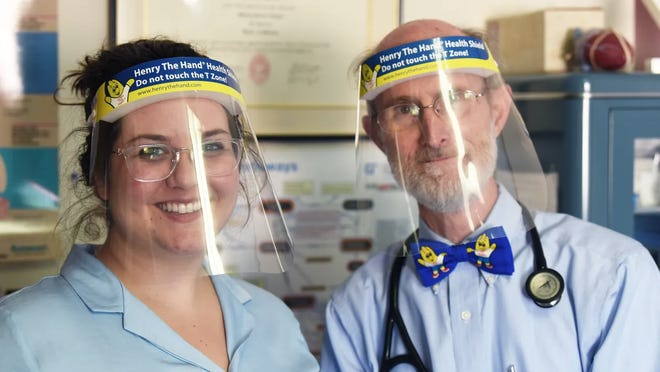 Dr. Will Sawyer, founder of the Henry the Hand Foundation, and the foundation's executive director, Raquel Zemtsov, pose with face shields.