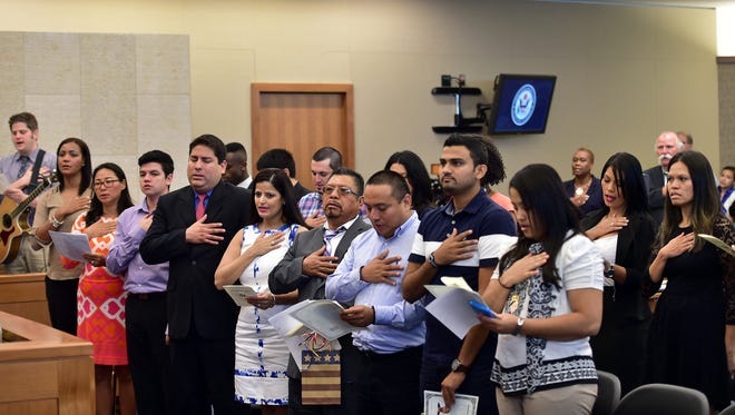New American citizens sing the National Anthem Thursday morning during a naturalization ceremony at the federal courthouse in Jackson.