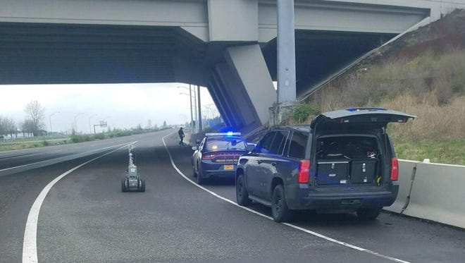 Oregon State Police bomb squad clears a suspicious package found on Interstate 5 near the Woodburn Interchange on Wednesday, March 21, 2018.