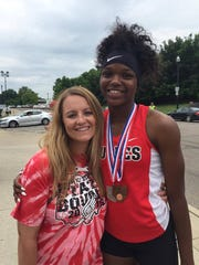 Former Hughes athletic director Jolinda Miller congratulates Tiona Lattimore after her state meet when she was in high school