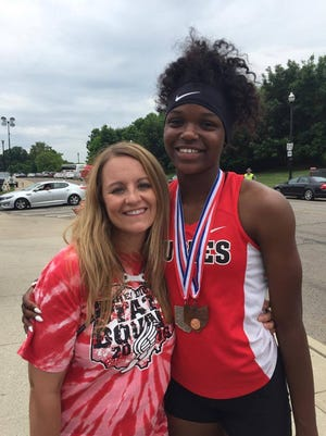 Hughes Athletic Director Jolinda Miller, one of four ADs of the year, congratulates Tiona Lattimore after her state meet last spring.