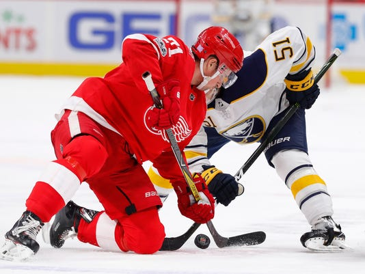 Detroit Red Wings center Dylan Larkin (71) and Buffalo Sabres center Kyle Criscuolo (51) vie for the puck during the first period of an NHL hockey game Friday, Nov. 17, 2017, in Detroit. (AP Photo/Paul Sancya)