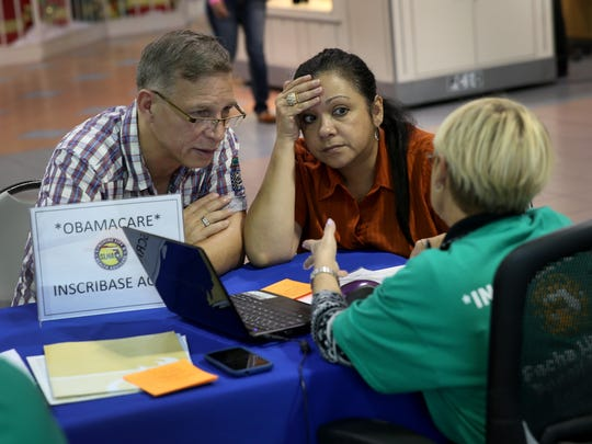 Angel Rivera (L) and his wife Wilma Rivera sit with, Amada cantera, an insurance agent with Sunshine Life and Health Advisors as they try to purchase health insurance under the Affordable Care Act at the kiosk setup at the Mall of Americas on December 22, 2013 in Miami, Florida.