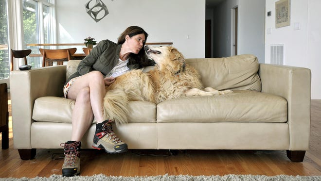Kelley Stadler sits with her dog, Mukki, at her home on Tuesday. Stadler suffered a stroke in 2010 while home alone and Mukki laid with her on the floor where she was stuck for 24 to 36 hours before being found. Stadler now suffers from aphasia, which affects her ability to communicate.