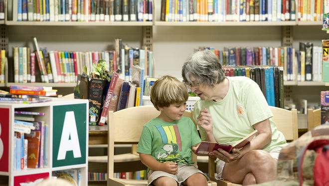 Maggie Winn reads a story to her grandson, Wayah Stone, 3, at the East Asheville Library earlier this year.