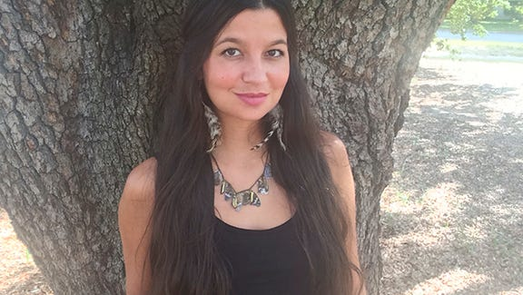 Artist Emmalee Sutton wearing her handmade feather earrings and butterfly wing necklace.