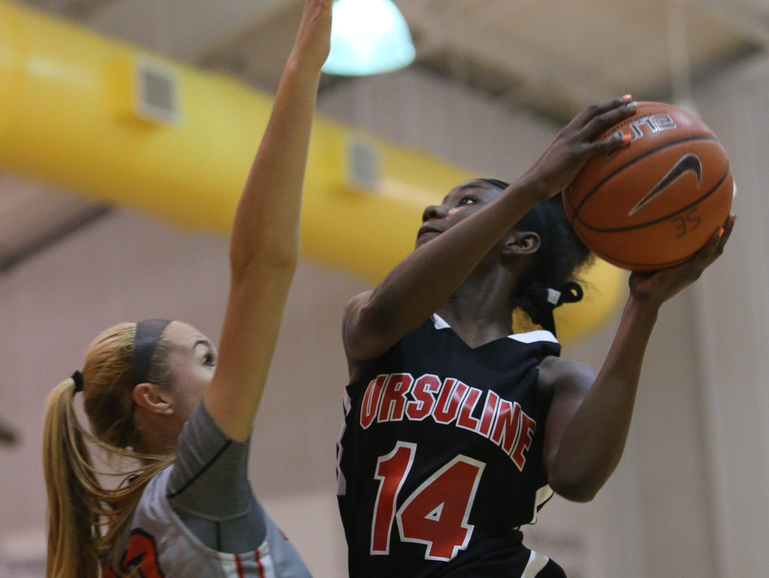 Ursuline forward Kryshell Gordy goes up for a layup over Long Island Lutheran forward Aislinn Flynn in the second quarter. Ursuline falls to Long Island Lutheran 52-55 in the semifinals of the Saint Francis Healthcare Cup of the Diamond State Classic at St. Elizabeth High School Tuesday.