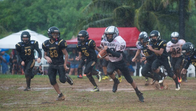 Raiders player Laethian Gumabon (29) runs the ball against the Saints during their Guam National Youth Football Federation Metgot Division game at Eagles Field in Mangilao on Aug. 21. The Benson Raiders won the game 13-0.