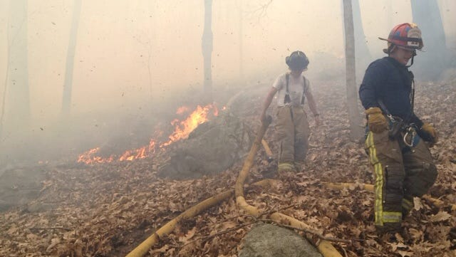 Firefighters battle a brush fire in woods on the grounds of the Morefar Golf Club in Southeast on April 22, 2014.