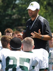 McNicholas coach Mike Orlando talks with his team after football practice last August.