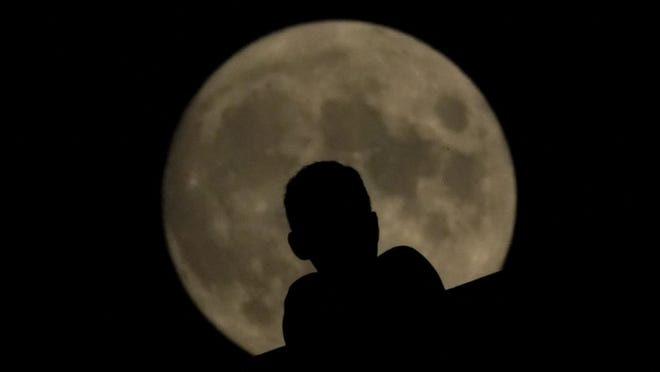 A man watches as the full moon rises  Sunday, Aug. 2, 2020, in Kansas City, Mo.