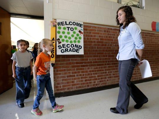 Cynthia Arceo takes her kids on a tour of the school