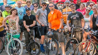 Physi, Inc. President Marty Boyer wears a bright orange Physi shirt as he leads a group of cyclists during a May Love the Cov  ride around town from the Goose Girl Fountain in Covington's MainStrasse Village.
