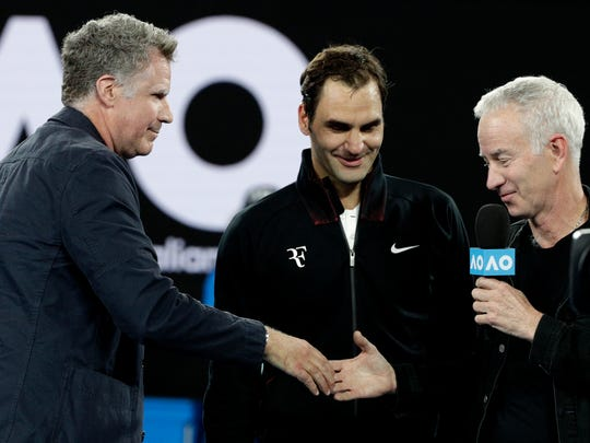 U.S. actor Will Ferrell, left, shakes hands with John McEnroe, right, after his interview with Switzerland's Roger Federer on Rod Laver Arena following his first round match against Slovenia's Aljaz Bedene at the Australian Open tennis championships in Melbourne, Australia, Tuesday, Jan. 16, 2018.