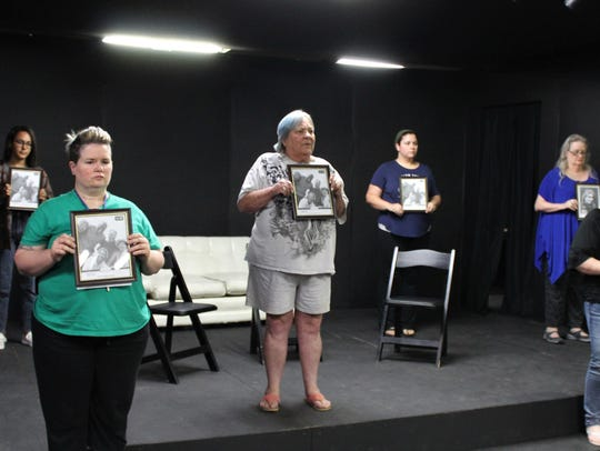 "Eight photographs of loved ones are lost are displayed for the audience in this rehearsal scene from ""The Door,"" one of four one-act plays to be presented in the Black Box Theatre at Abilene Community Theatre. From left: Kim Talafuse, Maya Jordan, Christine Schutter, Karen Reese, Kendra Brown, Crystal Hale, Susan Steele and Amanda Keith."
