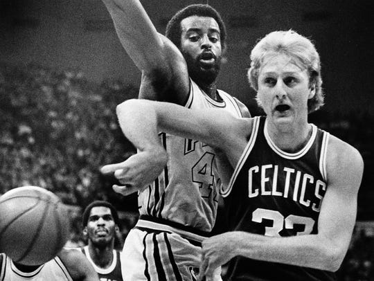 Boston Celtics forward Larry Bird, right, passes off