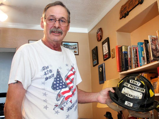 """In this file photo, Arthur """"Archie"""" Koenemundholds the helmet he was wearing during the cleanup of Sept. 11, 2001."""