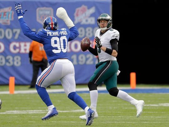 Philadelphia Eagles quarterback Nick Foles (9) looks to pass as New York Giants defensive end Jason Pierre-Paul (90) applies pressure during the first half of an NFL football game, Sunday, Dec. 17, 2017, in East Rutherford, N.J.