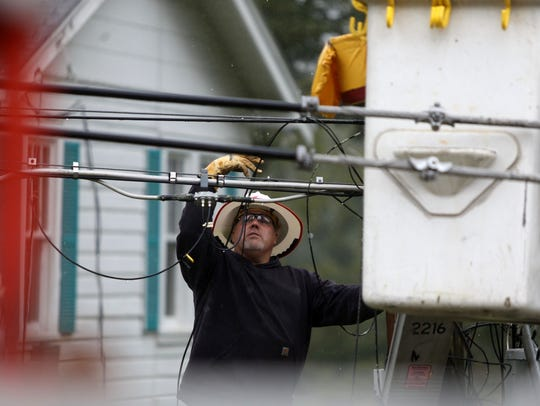 Lineman Heath Gebhardt works on a broken power pole