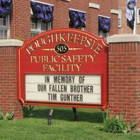 The City of Poughkeepsie Fire Department honors the death of one of its firefighters, Timothy Gunther, 54, with a message on the department's front lawn sign.