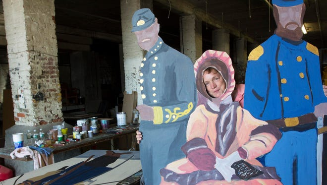 Artist Jill Snapp poses Sept. 8 in St. Albans with some of the figures she is in the process of painting for the St. Albans Raid Commemoration event.