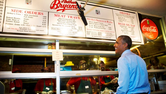 President Barack Obama orders barbecue at Arthur Bryant?s Barbeque restaurant in Kansas City, Mo., Tuesday, July 29, 2014, before meeting with four Kansas City residents who wrote him letters, over dinner a. According to the White House the Kansas City letter writers include a man who thanked Obama for student loan help he received, a single mother who described her challenges raising children and running a business, a teacher in a GED program and a woman who is active in her neighborhood association. (AP Photo/Jacquelyn Martin)