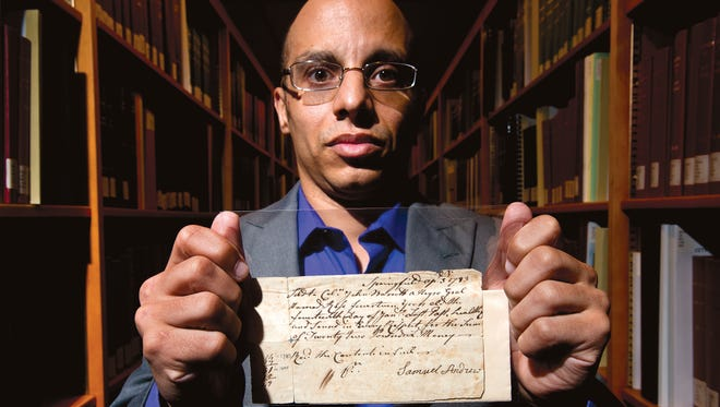 Harvey Amani Whitfield, associate professor of history at the University of Vermont, holds a 1783 bill of sale for a slave named Rose at the university's Special Collections in Burlington, Vt.