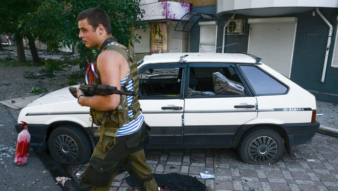 A pro-Russia rebel passes by a car  hit by shrapnel from a shell in the town of Donetsk, eastern Ukraine, on Aug. 27.