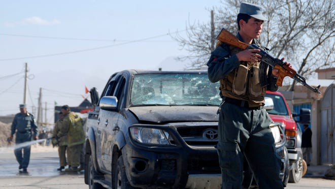 An Afghan policeman secures the area where a suicide bomber attacked the deputy governor of Balkh province in Mazar-e-Sharif, northern Afghanistan on Sunday.