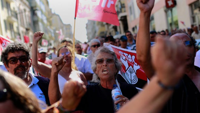 In this photo taken on May 9, 2014, people shout slogans during a protest by Portuguese local government workers outside the Sao Bento palace, Portugal's premier's official residence, in Lisbon.